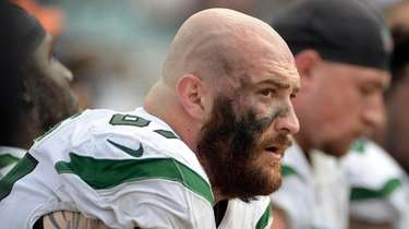 Jets offensive guard Brian Winters, left, sits on