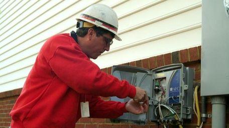 A Verizon technician installs a device, known as