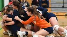 Manhasset girls volleyball teammates celebrate after defeating top-seeded