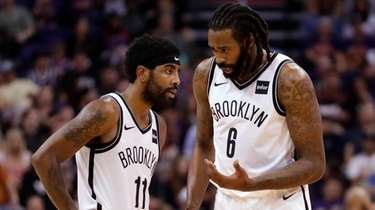 Brooklyn Nets guard Kyrie Irving talks with center