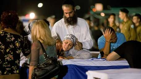 Relatives mourn over the coffin of Itzik Colangi,