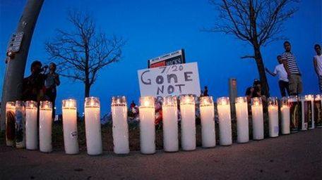 As night falls, candles sit illuminated along the
