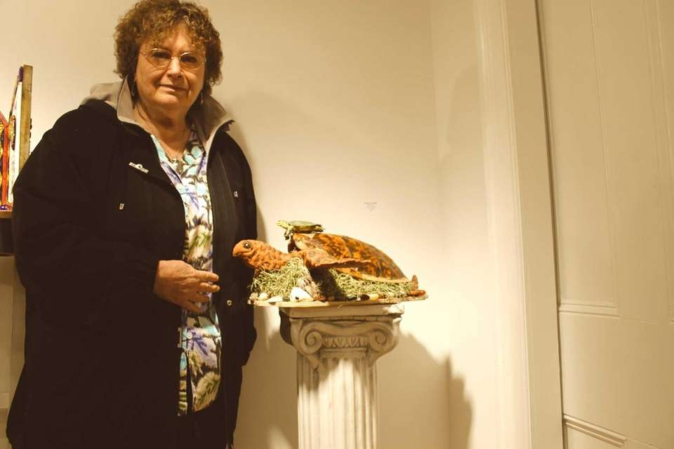 "Barbara Schneider poses with ""Re-incarnation,"" a piece consisting"