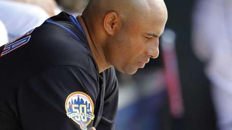 Miguel Batista sits in the dugout in the