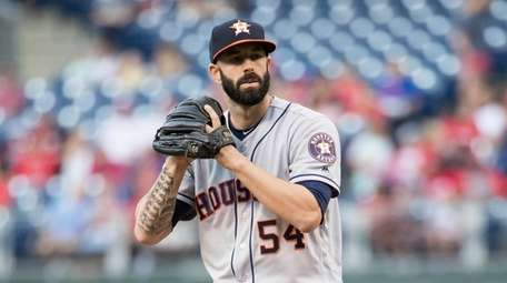 Mike Fiers throws a pitch during the first