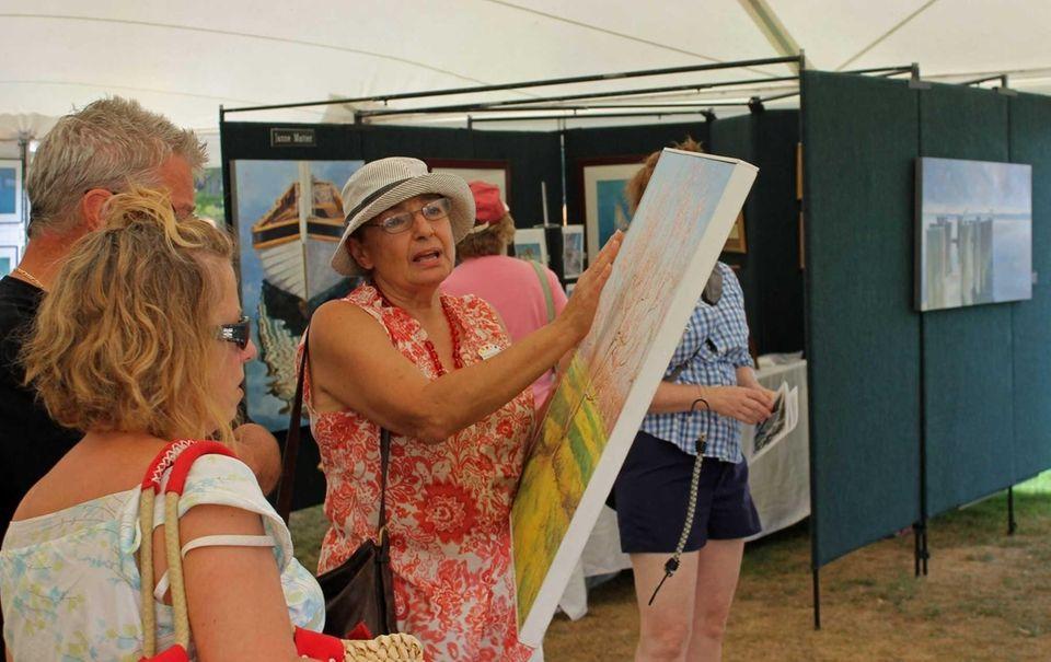 Carol Gold, 69, of Mattituck, shows customers a