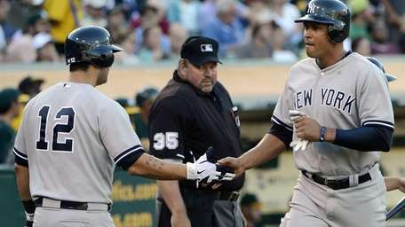 Alex Rodriguez is congratulated by Eric Chavez after