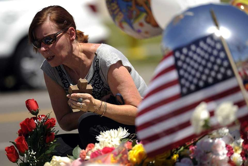 Cheryl deBeaubien, 54, places flowers at a memorial