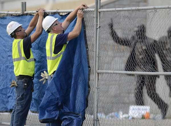 Workers place a tarp on a fence in