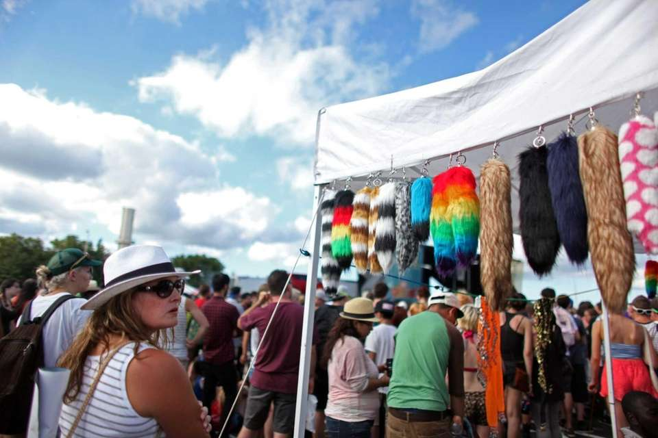 Concertgoers spend time at vendor tents Saturday during