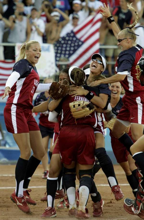 The United States softball team jumps on pitcher