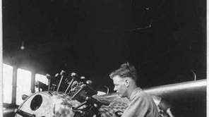 1927: Charles Lindbergh works on the engine of