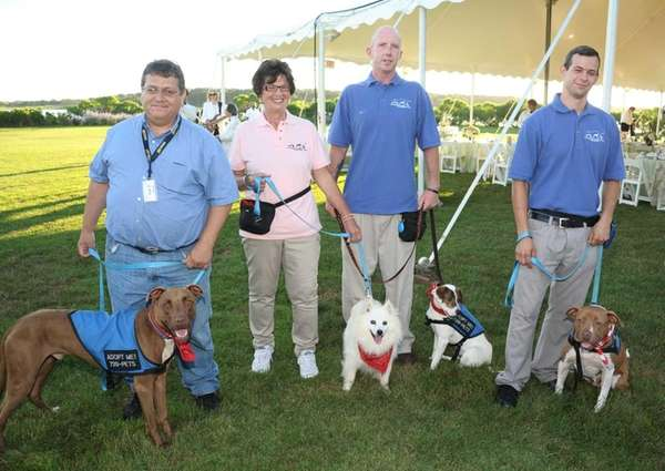 Animal trainers and dogs for adoption attend the