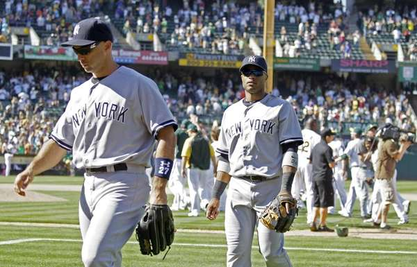 Raul Ibanez, left, and Robinson Cano walk off