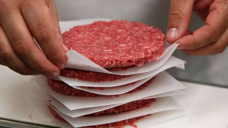 A worker stacks ground beef patties at a