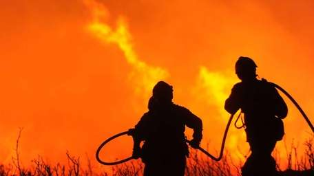 Firefighters try to extinguish a wildfire in Ller