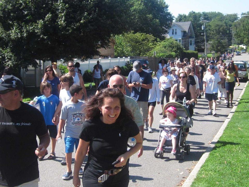 Hundreds walk along Elm Street in Huntington to