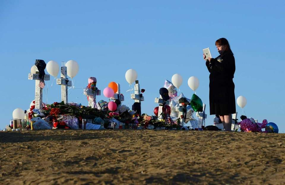 A woman stands at the makeshift memorial to