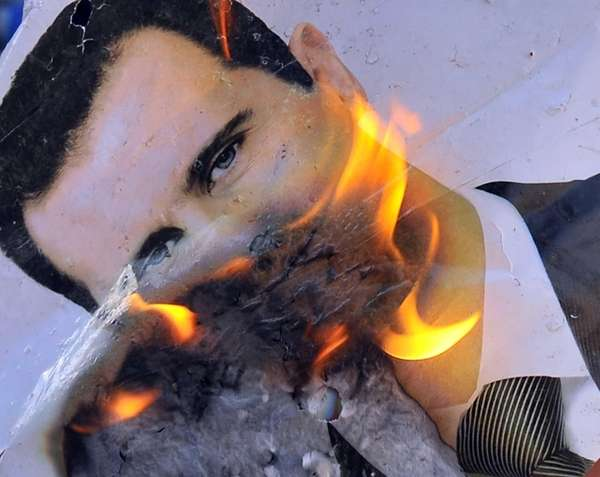 A portrait of Syrian President Bashar al-Assad burns