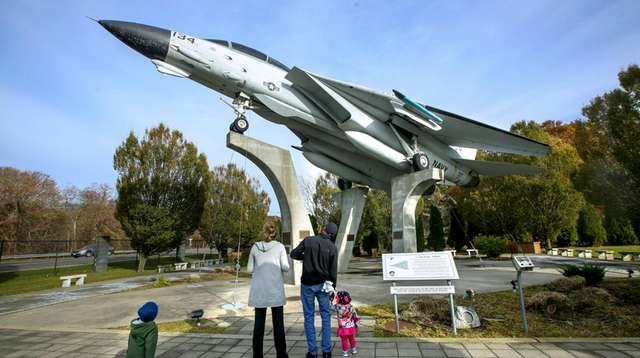 A family looks at the F-14 fighter jet