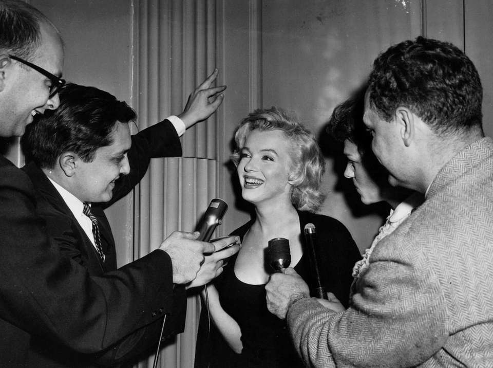 Marilyn Monroe flashes a radiant smile behind microphones