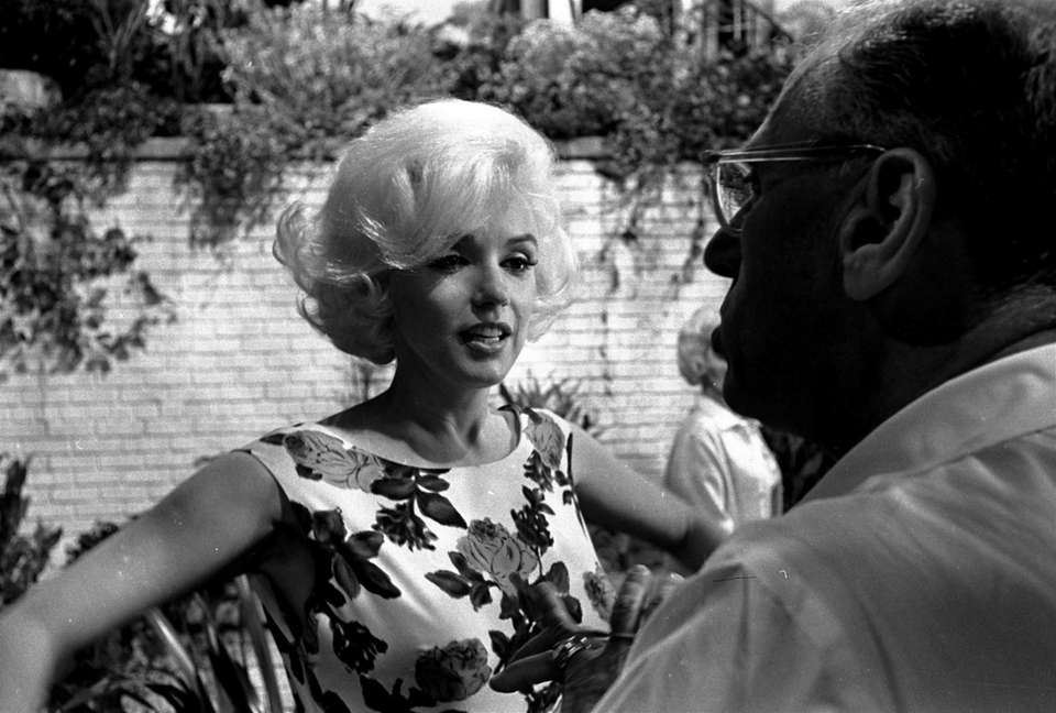 Director George Cukor talks with Marilyn Monroe in