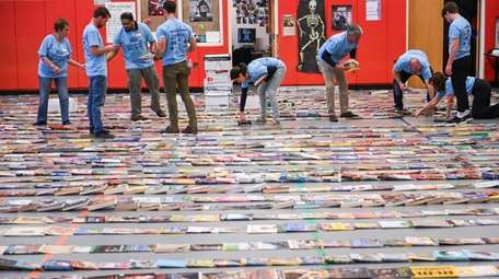 Volunteers line up books into rows at La