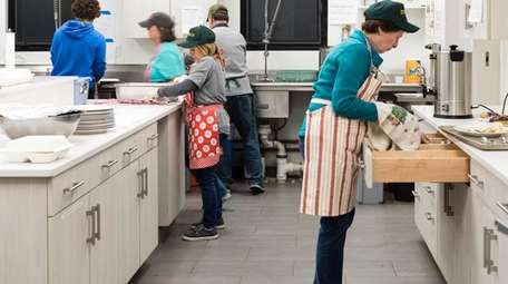 Volunteers clean the kitchen after serving 47 meals