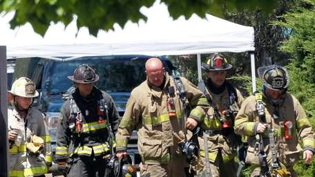 Firefighters walk to shade as temperatures near 100