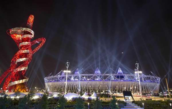 Searchlights shine over the Olympic Stadium during a