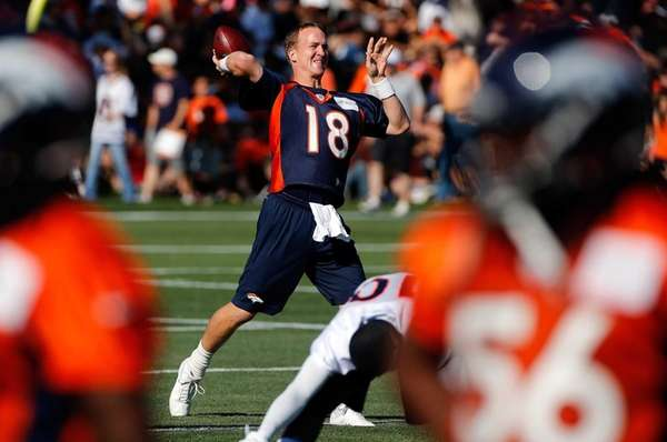 Quarterback Peyton Manning makes a pass during training