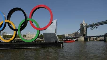 Olympic Rings hang from the Tower Bridge beyond