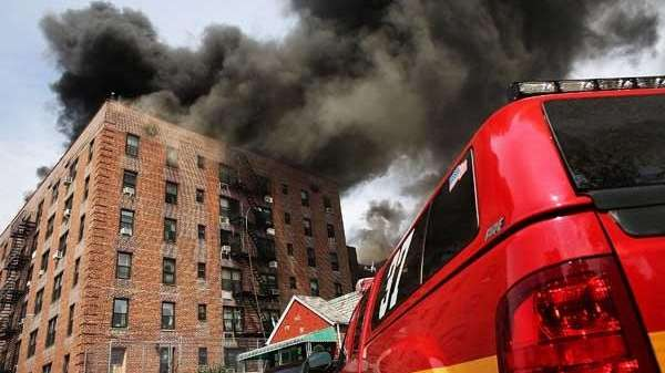 Firefighters battle a fire at a seven-story apartment