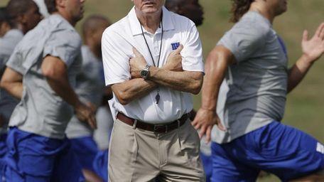Giants head coach Tom Coughlin, center, looks on