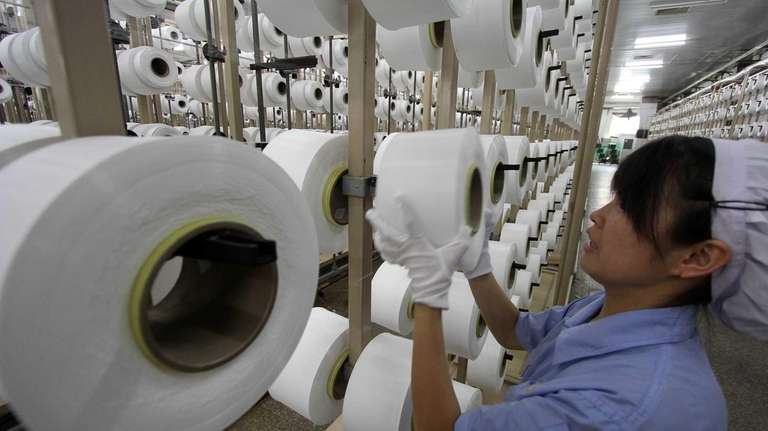 A Chinese worker monitoring a thread-making machine at