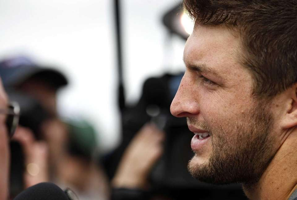 Tim Tebow talks to reporters during the first