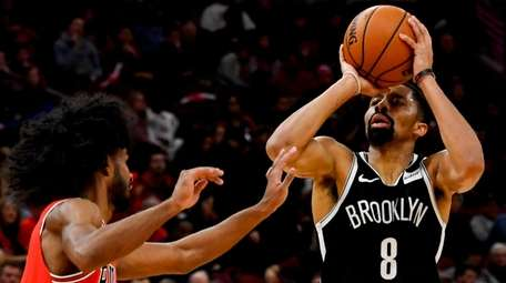 Nets guard Spencer Dinwiddie shoots next to Chicago