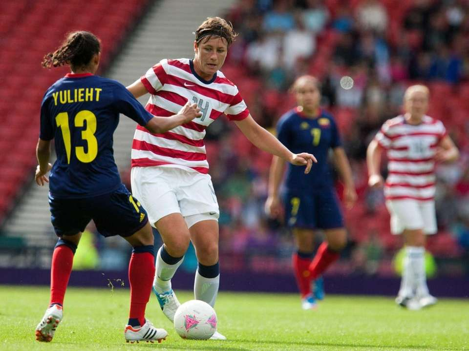 Abby Wambach, second from left, is tackled by