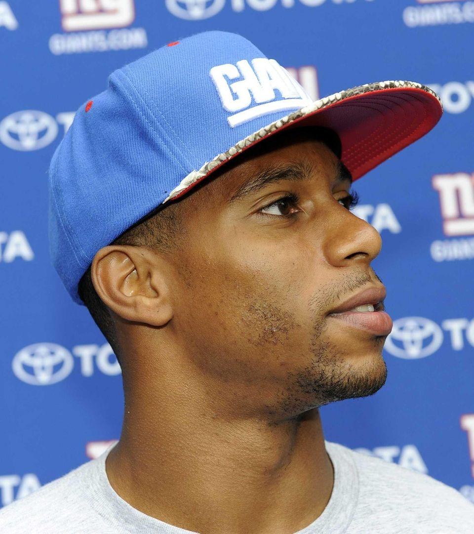 Giants wide receiver Victor Cruz talks with reporters