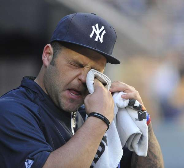 Joba Chamberlain wipes his face during a game