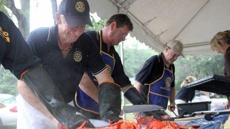 Volunteers prepare lobsters for the crowd attending the