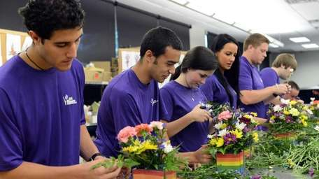 Interns at 1-800-Flowers assemble arrangements during training at