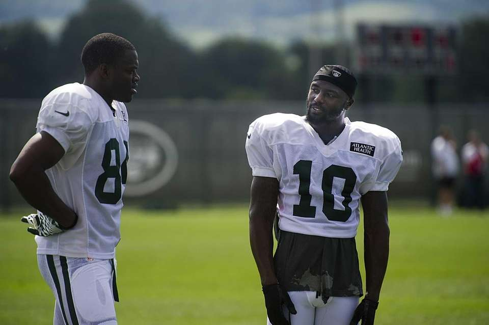 Santonio Holmes helps teammate WR Stephen Hill with