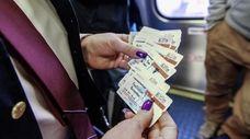 A worker holds LIRR tickets aboard a Babylon-bound