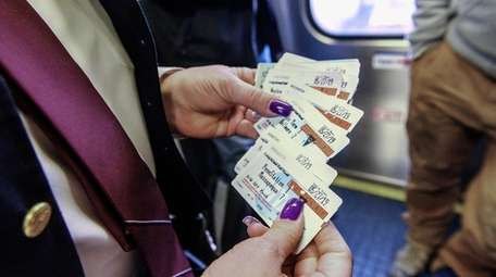A worker holds LIRR tickets aboard a Babylon-bound