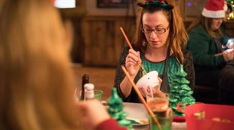 Danielle Gagliardi paints a ceramic Christmas tree at