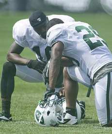 Santonio Holmes, left, talks with Bilal Powell during