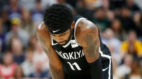 Nets guard Kyrie Irving looks down at the