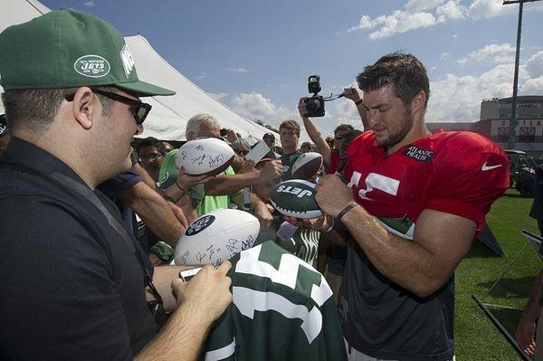 Jets quarterback Tim Tebow signs autographs for Jet