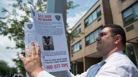 A member of the NYPD places a reward